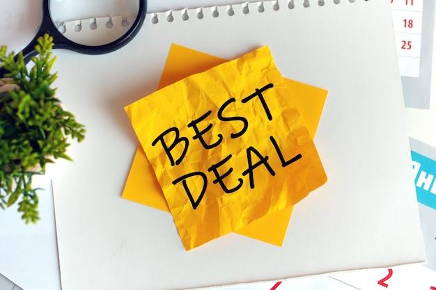 Scrivere il miglior affare su carta gialla spiegazzata, posto di lavoro, brainstorming. sfocatura. lettere rosse.