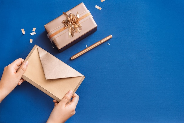 Scrivere auguri di natale con scatola d'oro e ghirlanda