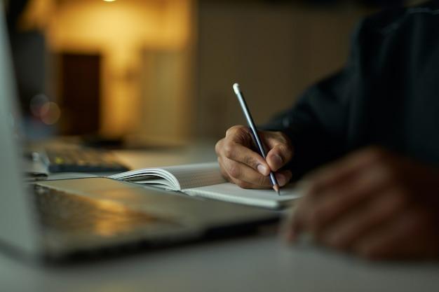 Scrivere idee ravvicinata delle mani di uno studente maschio che prende appunti sul suo quaderno mentre studia