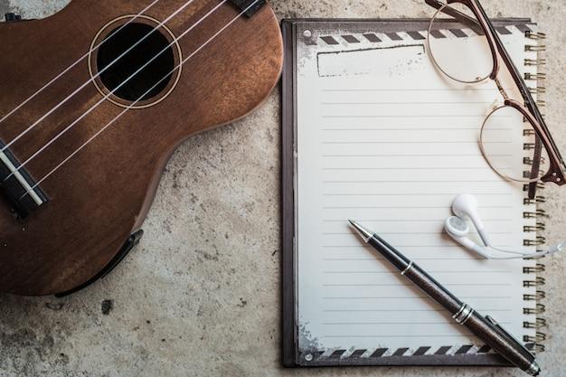 Scrivere musica con ukulele, blocco note e cuffie sul pavimento di cemento. effetto filtro vintage retrò.
