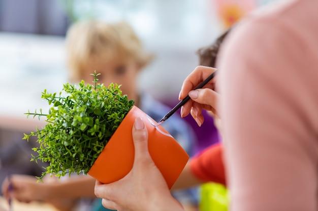 Scrivere sul vaso. primo piano dell'insegnante che tiene un vaso di fiori con una pianta verde che scrive sul vaso alla lezione di ecologia