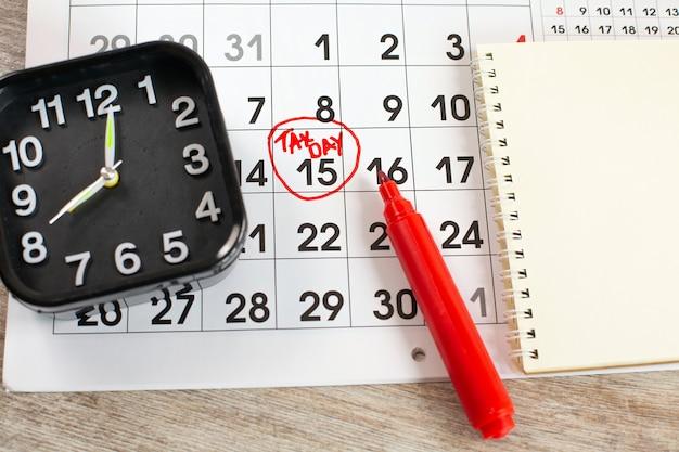 Scrivere il giorno delle tasse il 15 aprile del calendario mensile cerchiato nel cerchio con un pennarello rosso con taccuino e sveglia.