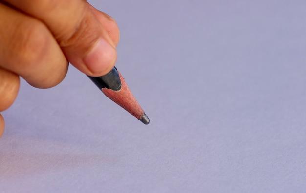 Scrivere con una matita nera, messa a fuoco selezionata, isolata su sfondo bianco. concetto di educazione