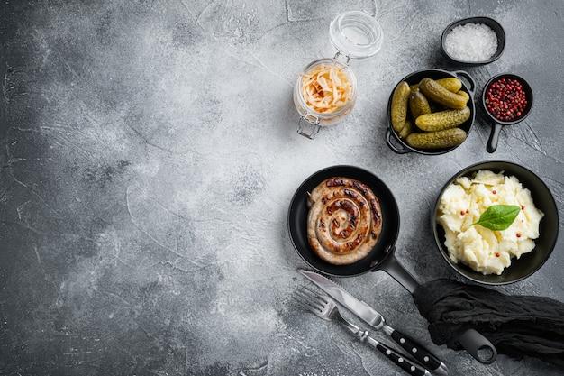 Wurstel o bratwurst con cavolo fermentato, cetrioli sottaceto e spezie in padella in ghisa, su sfondo grigio, vista dall'alto laici piatta, con spazio per testo copyspace