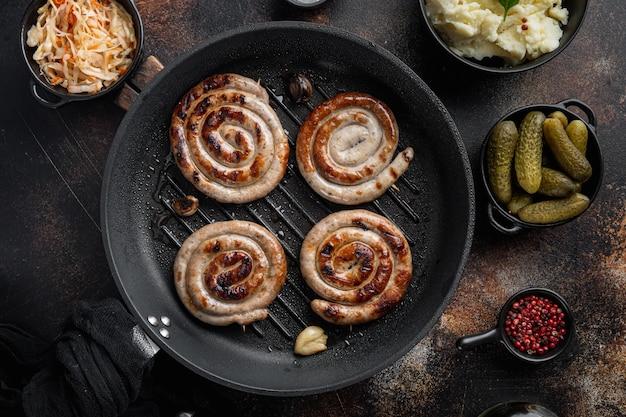 Wurst o bratwurst con cavolo fermentato, cetrioli sottaceto e spezie in padella in ghisa, sul vecchio scuro tavolo rustico, vista dall'alto laici piatta