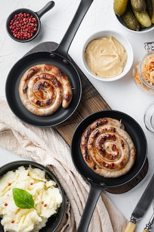 Wurstel o bratwurst con cavolo fermentato, cetrioli sottaceto e spezie in padella in ghisa, sul tavolo bianco, vista dall'alto laici piatta