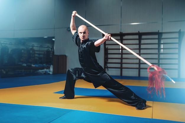 Maestro di wushu che si allena con la lancia, arti marziali. l'uomo in panno nero posa con la lama