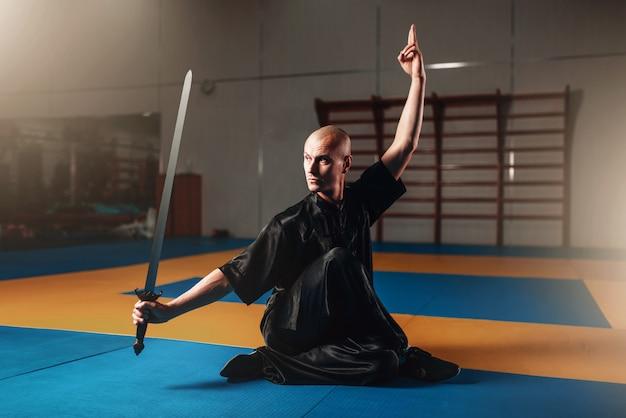 Maestro di wushu che si allena con la spada, arti marziali