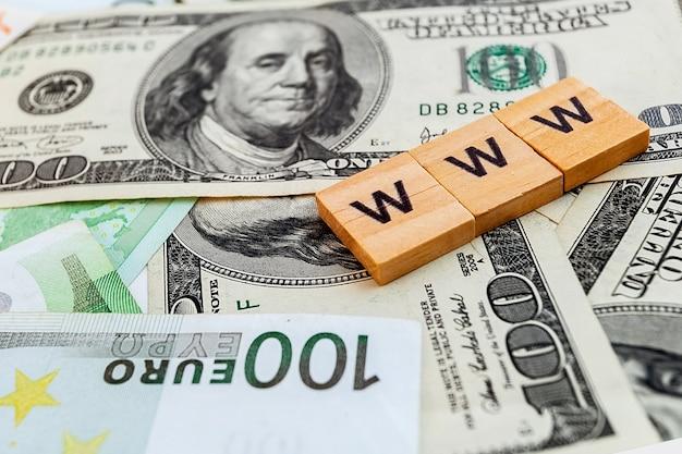 Iscrizione www su cubi di legno sulla trama di dollari americani e banconote in euro