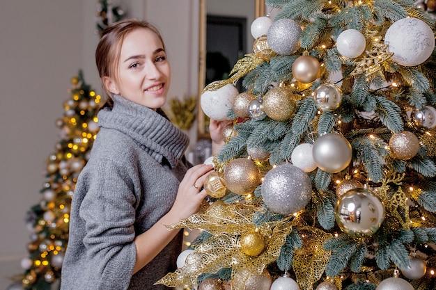 X-mas, vacanze invernali e concetto della gente - giovane donna felice che decora l'albero di natale a casa.