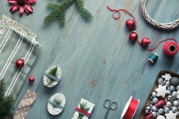 Sfondo di natale su legno screpolato con ramoscelli di abete dell'albero di natale, scatole regalo e decorazioni in rosso, bianco e verde.