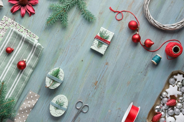 Sfondo di natale con ramoscelli di abete albero di natale, scatole regalo e decorazioni in rosso e verde.