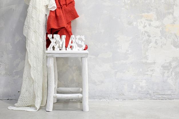 Parola di natale sul tavolo accanto a coperte di lana e muro di cemento grigio