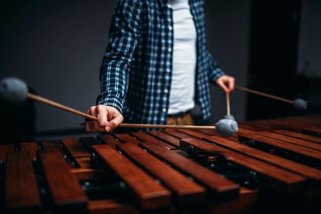 Mani del giocatore di xilofono con bastoni, suoni di legno