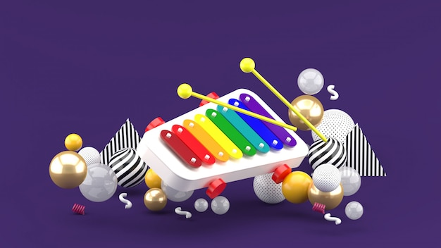 Xilofono giocattolo tra palline colorate su spazio viola