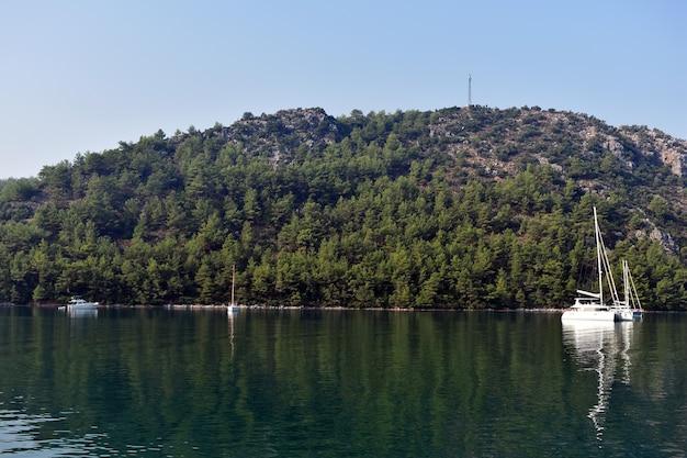 Lo yacht naviga sul mare lungo le montagne