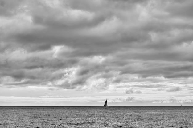 Yacht nel mare e nel cielo nuvoloso - seascape minimalista in bianco e nero