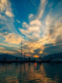 Yacht in mare al tramonto. silhouette di uno yacht sullo sfondo del sole al tramonto all'orizzonte