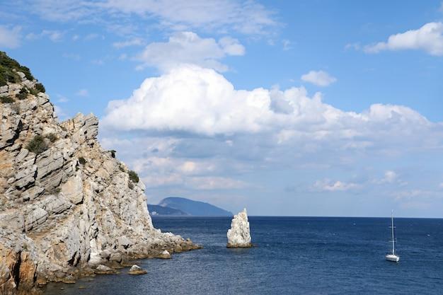 Yacht che cammina sul mare. costa rocciosa. cielo sereno e soleggiato con soffici nuvole.