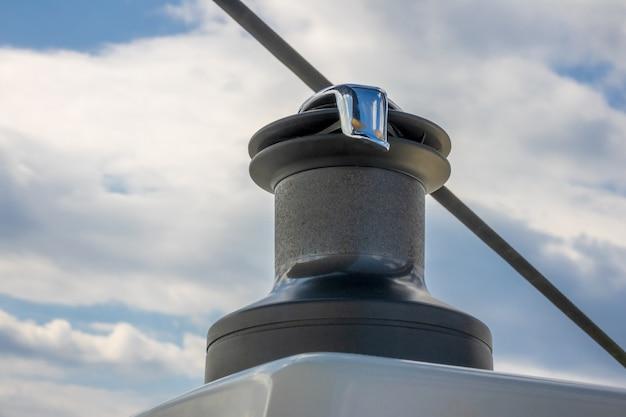 Primo piano dell'argano dell'yacht su una priorità bassa del cielo blu sfocato con le nuvole