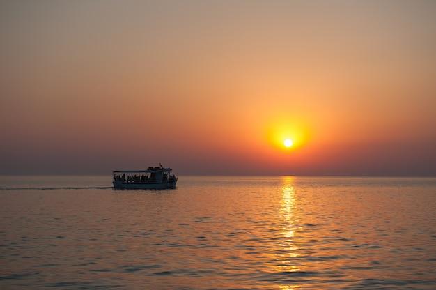 Yacht con i turisti al tramonto con gli uccelli che volano via