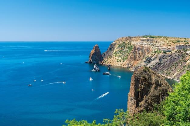 Yacht in mare. paesaggio di mare con yacht e costa rocciosa.
