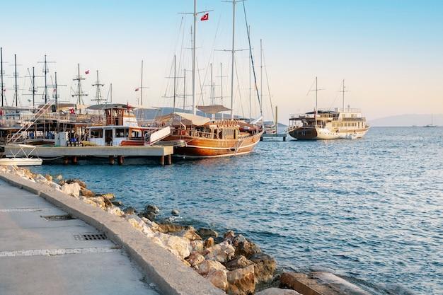 Yacht e navi nella baia di bodrum, mar egeo turchese al tramonto.
