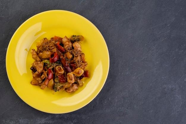 Yakisoba con carne di pollo su un piatto giallo su una pietra di ardesia scura - vista dall'alto