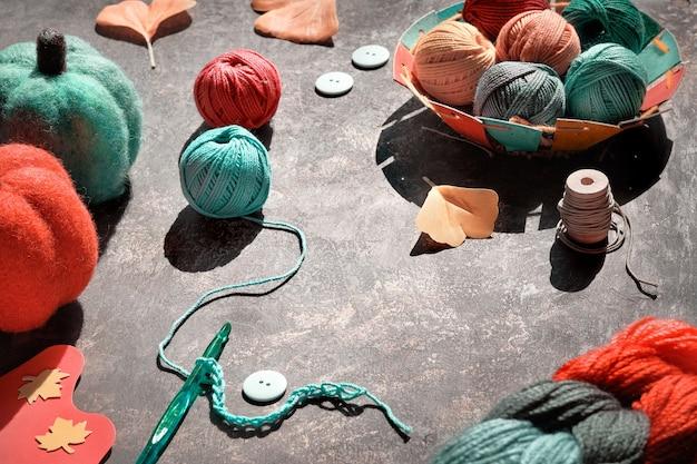 Gomitoli di filato, uncinetto con filo, bottoni, zucche decorative