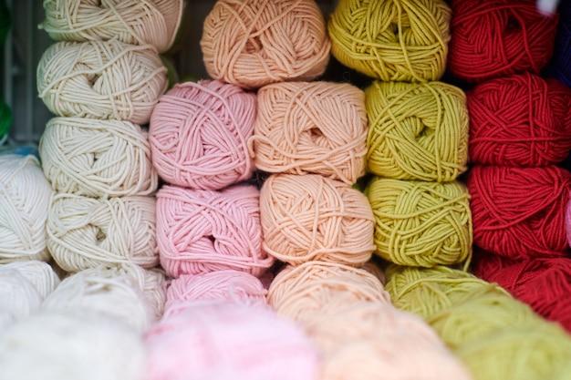 Filati o gomitoli di lana sugli scaffali in negozio per maglieria e ricamo, primi piani. accessori per merceria negli scaffali dei negozi di tessuti