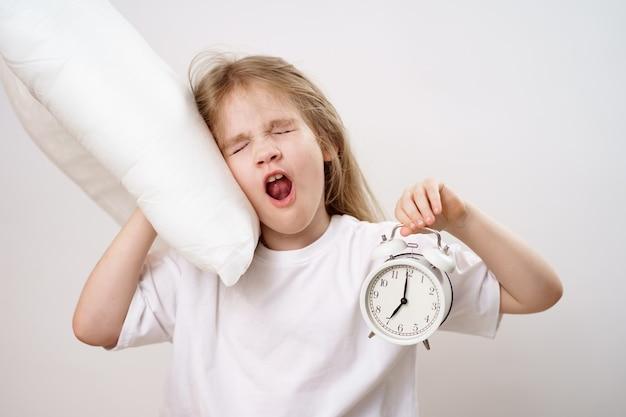 Una ragazza che sbadiglia abbraccia un cuscino e una sveglia su bianco