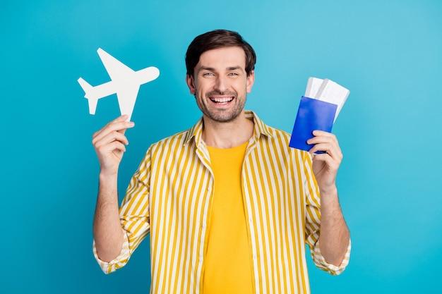 Sì, confini aperti. l'uomo allegro positivo tiene i biglietti aerei della carta cartacea si diverte a viaggiare all'estero quarantena covid indossa un abito bianco isolato su uno sfondo di colore blu