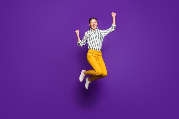 Si! foto a figura intera di pazza bella signora che salta in alto celebrando la vittoria alzando i pugni fan di sport indossare pantaloni gialli camicia a righe isolato sfondo di colore viola