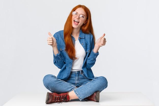 Sì, provaci. ragazza adolescente rossa eccitante e impertinente di bell'aspetto con taglio di capelli rosso voluminoso, seduto a gambe incrociate sul pavimento, mostrando il pollice in su e dicendo di sì, raccomandare, approvare qualcosa