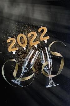 L'anno 2022 scritto con candele dorate e due bicchieri di champagne frizzante su sfondo nero