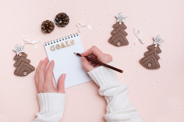 Obiettivi dell'anno. le mani delle donne scrivono con una matita in un taccuino