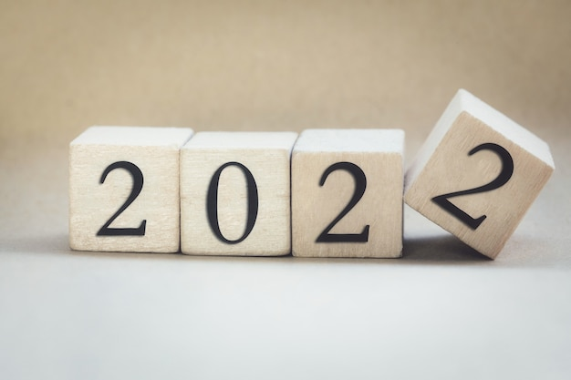 L'anno scritto su cubi di legno che lanciano le dita di anno in anno concetto di capodanno sfondo a partire da ...