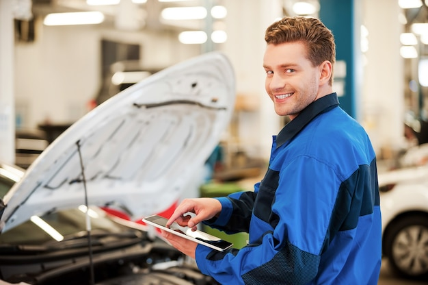 Anni di esperienza meccanica. giovane fiducioso che lavora su tablet digitale e sorride mentre si trova in officina con l'auto sullo sfondo