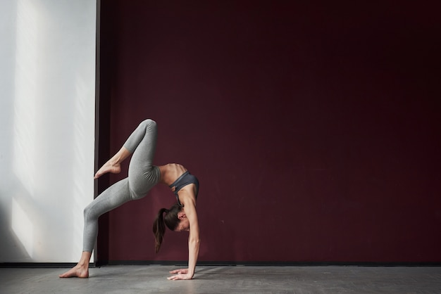 Anni di formazione. la ragazza con un buon tipo di corpo fitness ha esercizi nella stanza spaziosa