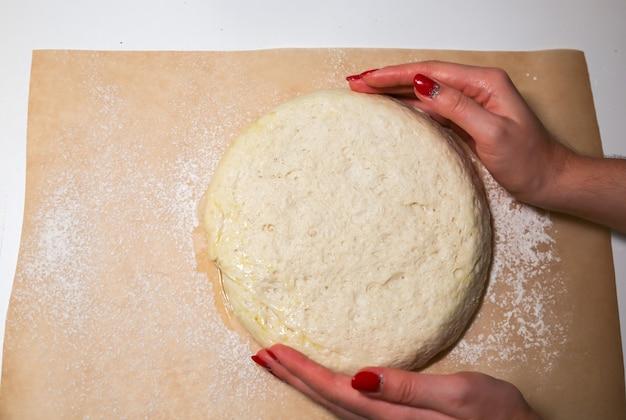 Pasta lievitata sul tavolo. concetto di cottura. idee di cucina. le mani della donna che producono cibo fatto in casa. impastare farina e acqua.