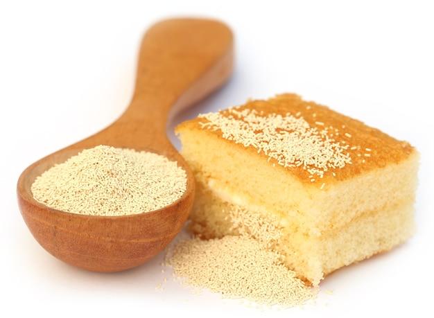 Lievito in un cucchiaio di legno con pane su sfondo bianco