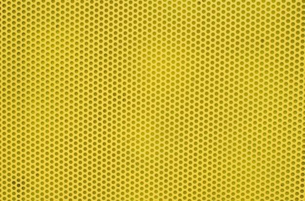 Sfondo astratto giallo su base di metallo, trama della superficie gialla con molti fori rotondi.