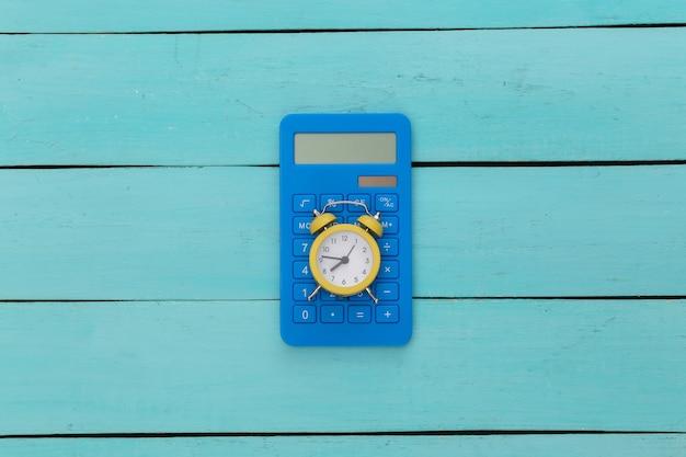 Sveglia gialla e calcolatrice su fondo di legno blu.