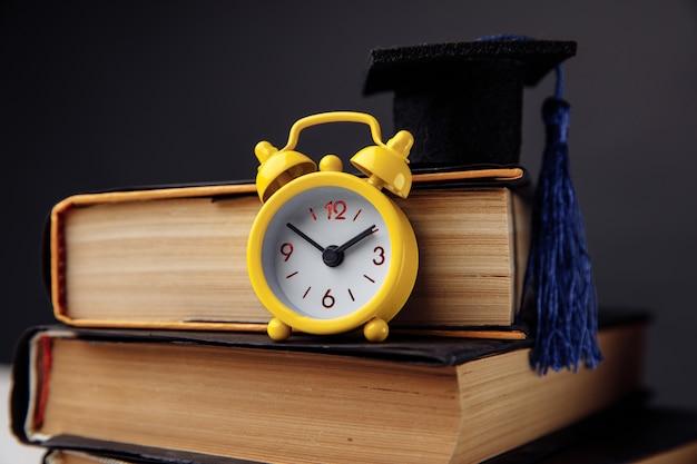 Sveglia gialla, berretto di laurea e libri sul tavolo. concetto di educazione.