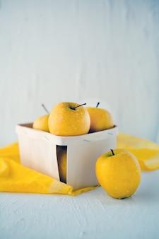 Mele gialle al cesto su sfondo bianco concetto per una sana alimentazione vista frontale
