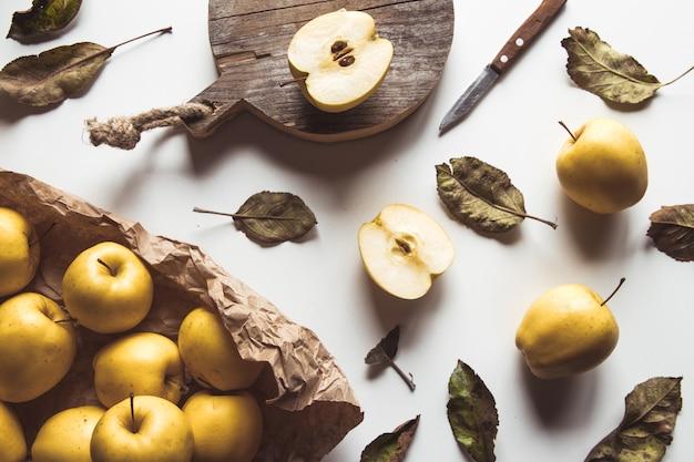 Mele gialle su una tavola a fette in stile vintage. foglie, cibo, cibo sano, vegano, prodotto agricolo.