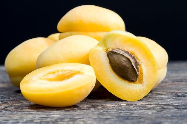 Mucchio di albicocche gialle con albicocca tagliata