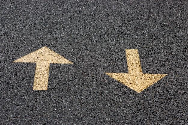 Frecce gialle sulla strada asfaltata, avanti e indietro