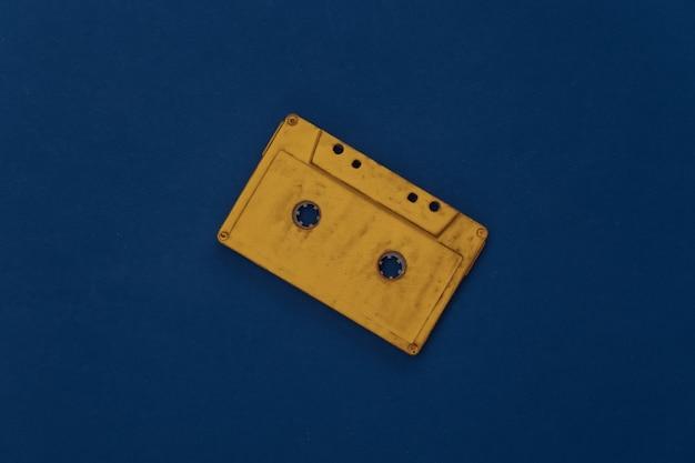 Cassetta audio gialla su sfondo blu classico. colore 2020. vista dall'alto
