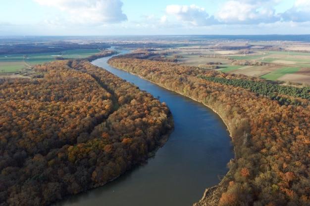 Foresta di autunno giallo e fiume blu, vista dall'alto, paesaggio autunnale